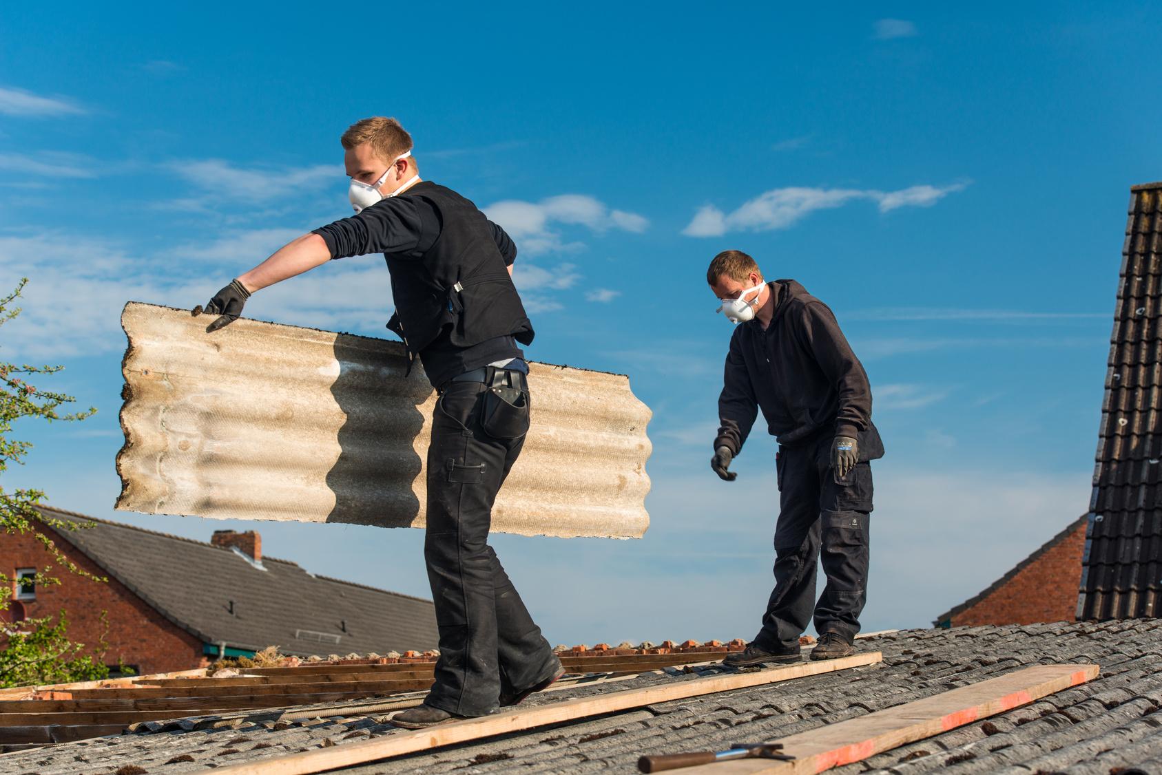 Artisans rénovant toiture.