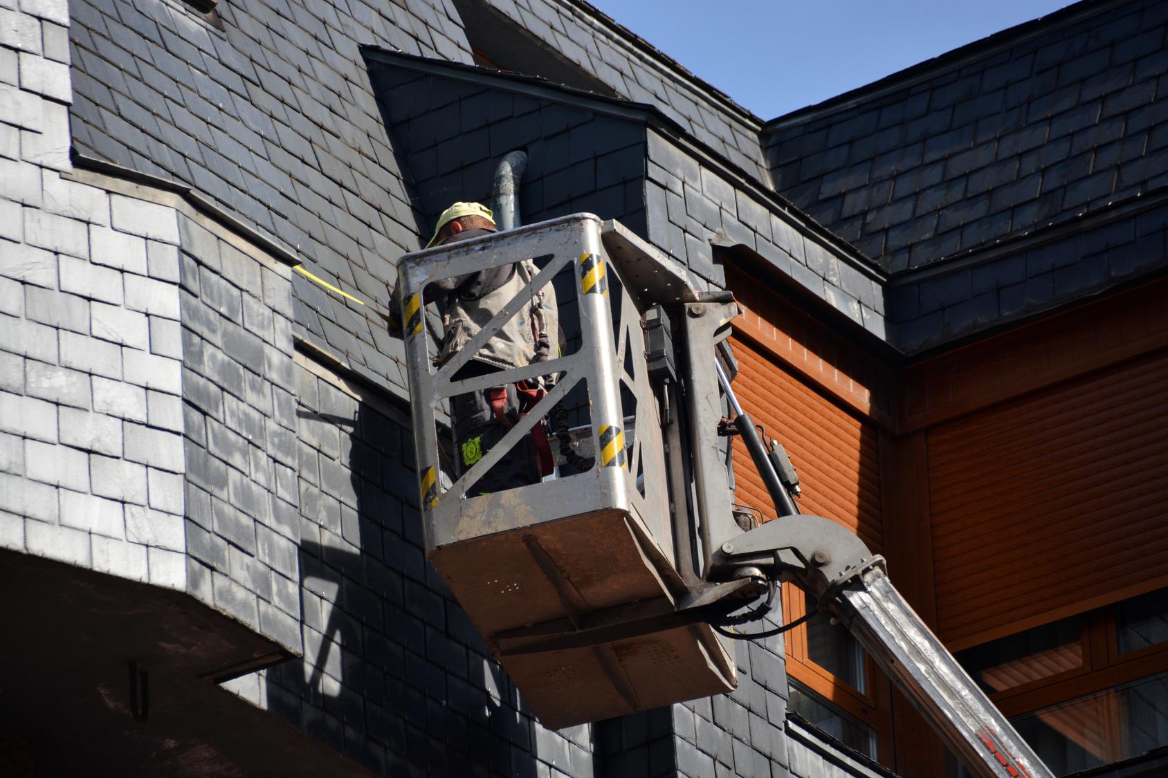 Artisan réparant toit hauteur.